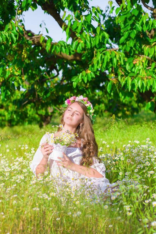 Flickan med långt hår som bär en krona av tusenskönor på fältet royaltyfri fotografi