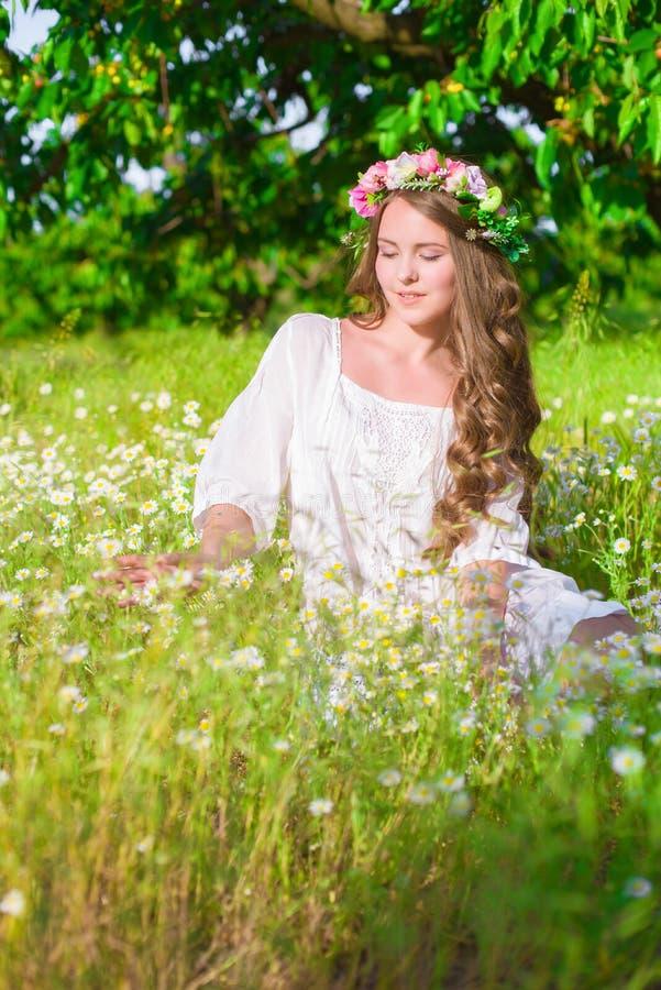 Flickan med långt hår som bär en krona av tusenskönor på fältet royaltyfria foton