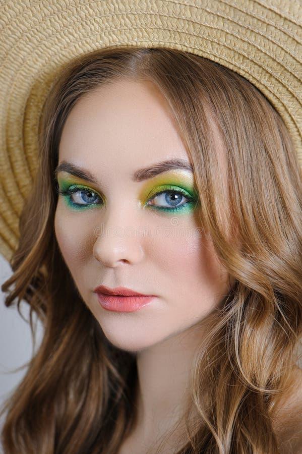 Flickan med ljus makeup som poserar i en sugrörhatt arkivfoton