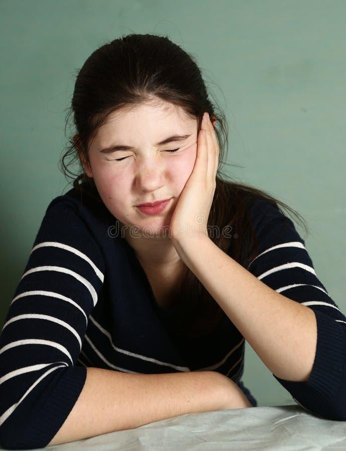 Flickan med mörkt hår har sträng toothace arkivbild