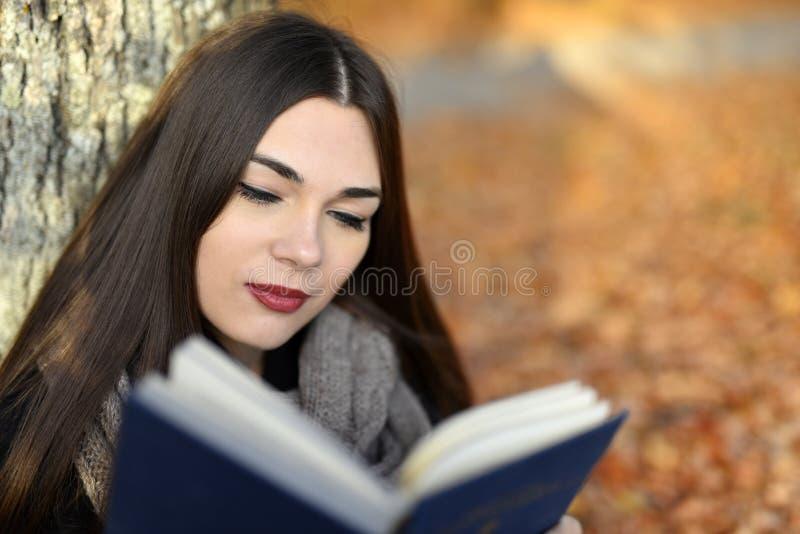 Flickan med mörkt hår läser den blåa boken i höst parkerar royaltyfri bild