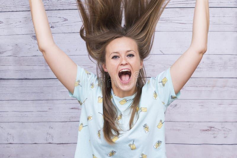 Flickan med ovårdade långa hårskrin, jublar arkivbilder