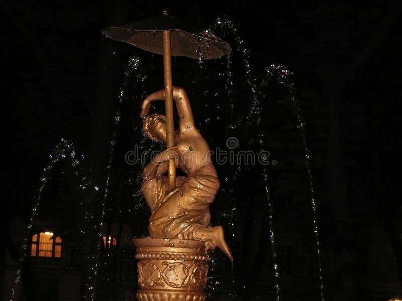 Flickan med paraplyet under springbrunnen sprutar ut royaltyfri foto