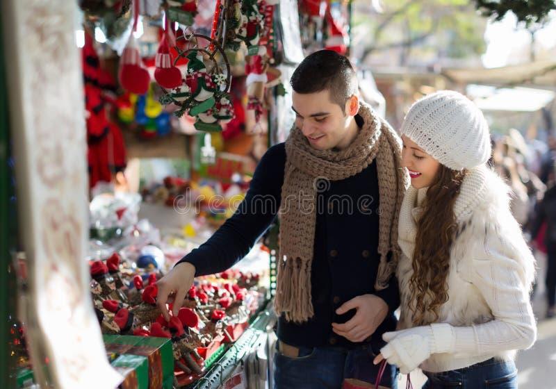 Flickan med pojkvännen som väljer catalan jul för tradition, souven royaltyfria bilder