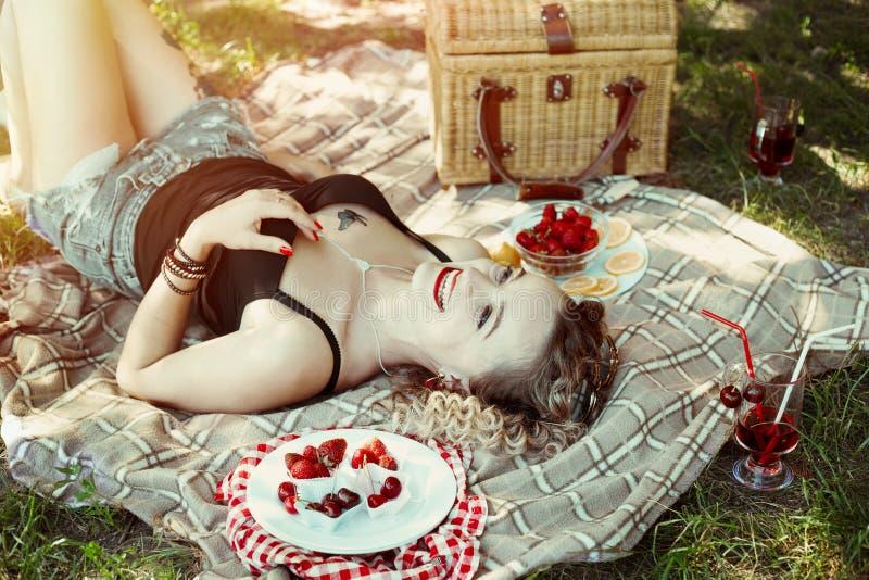 Flickan med röda kanter äter jordgubben på picknick royaltyfria foton