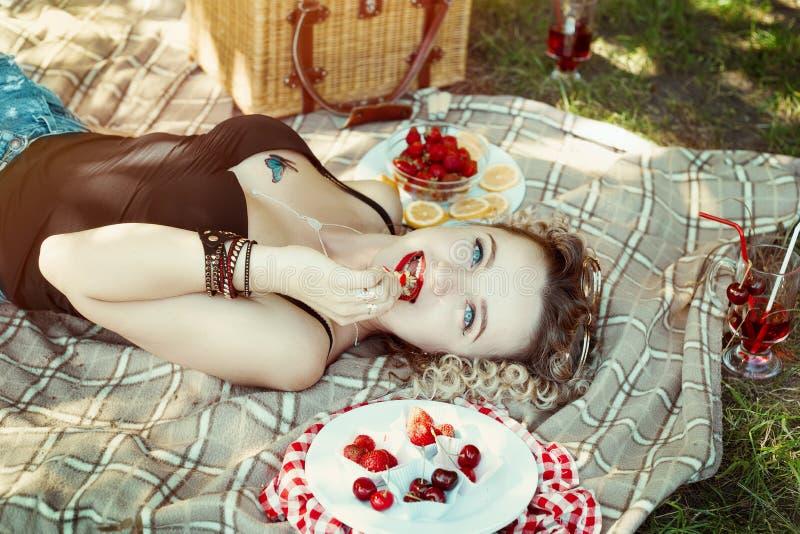 Flickan med röda kanter äter jordgubben på picknick arkivfoto