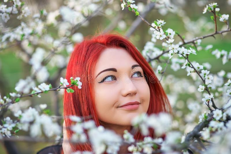 Flickan med rött hår inhalerar doften av blommorna av trädet royaltyfri foto