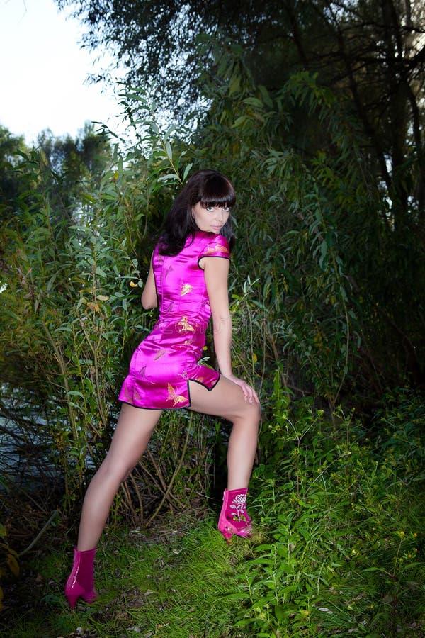 Flickan med stora ögon i rosa färger klär på bakgrund av grön lövverk royaltyfri bild