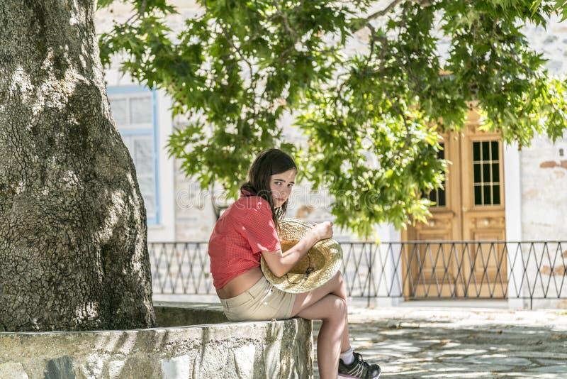 Flickan med sugrörhatten i här räcker sammanträde under ett träd royaltyfri foto
