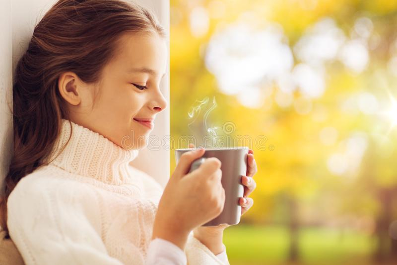 Flickan med te rånar det sittande hemmastadda fönstret i höst royaltyfria bilder