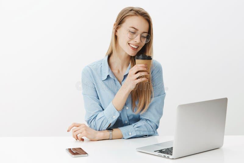 Flickan missbrukade för att arbeta och att le i huvudsak som att läppja kaffe som sitter nära bärbara datorn och smartphonen som  arkivbild