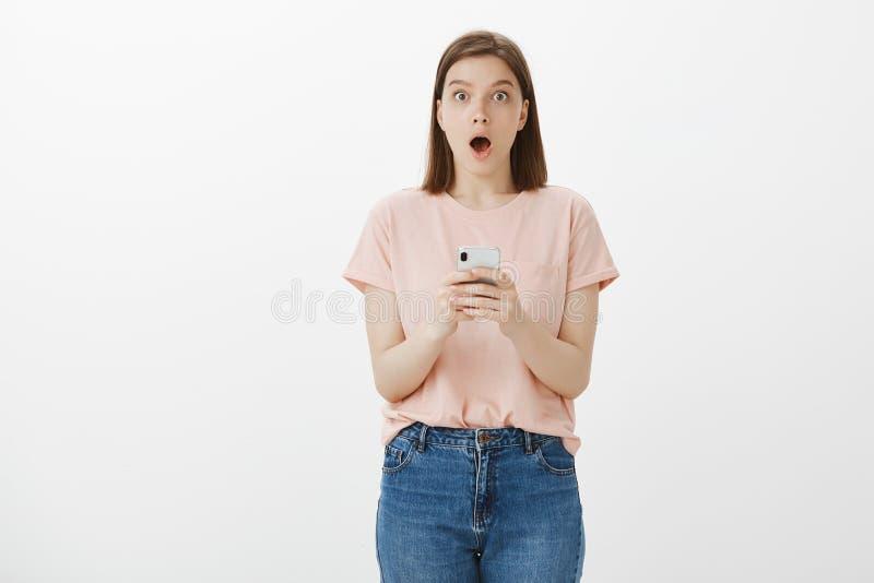 Flickan mottog emailbekräftelse som hon passerade examina och att vara den chockade och förvånade hållande smartphonen och tappak royaltyfria bilder