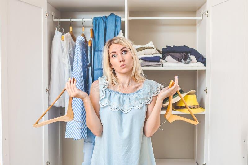 Flickan nära garderoben med kläder väljer vad för att bära ingenting att bära design royaltyfria bilder
