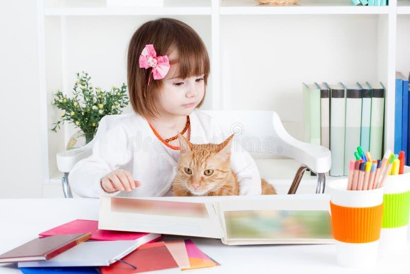 Flickan och en katt läste en bilderbok arkivfoto