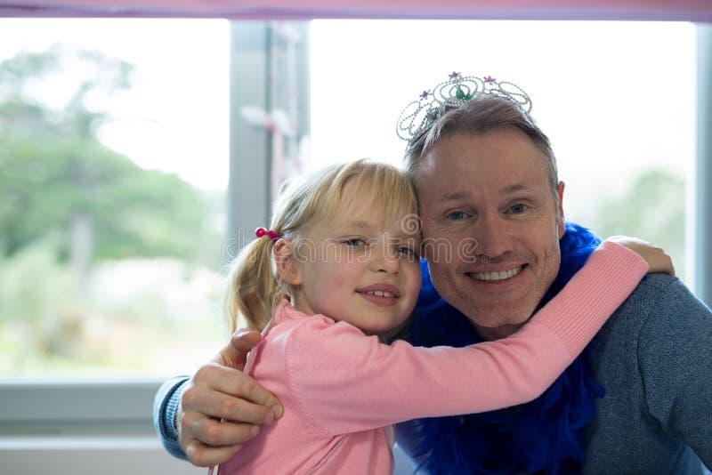 Flickan och fadern klädde som fen som omfamnar sig fotografering för bildbyråer