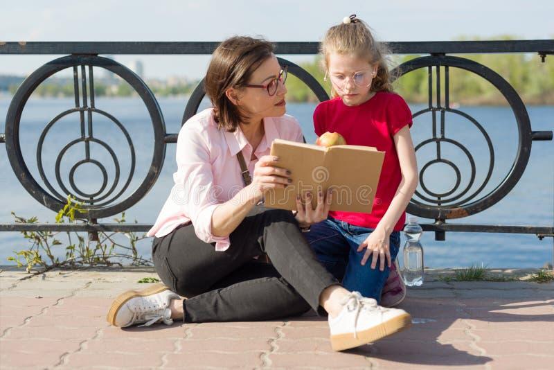 Flickan och fostrar läsning boka royaltyfria bilder