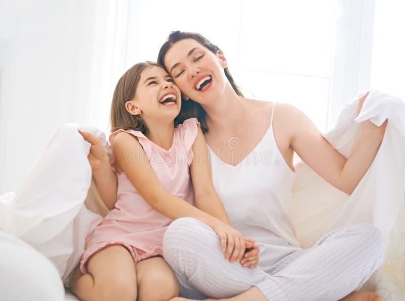 Flickan och hennes moder tycker om solig morgon royaltyfri bild