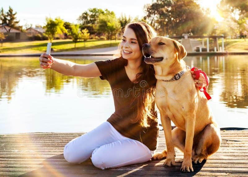 Flickan och hunden Selfie på parkerar arkivfoto