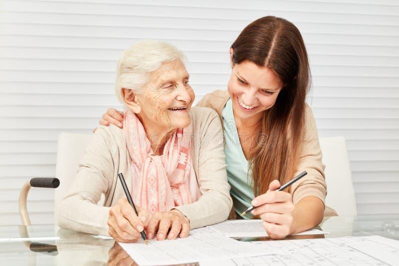 Flickan och pensionären löser pussel tillsammans arkivbilder