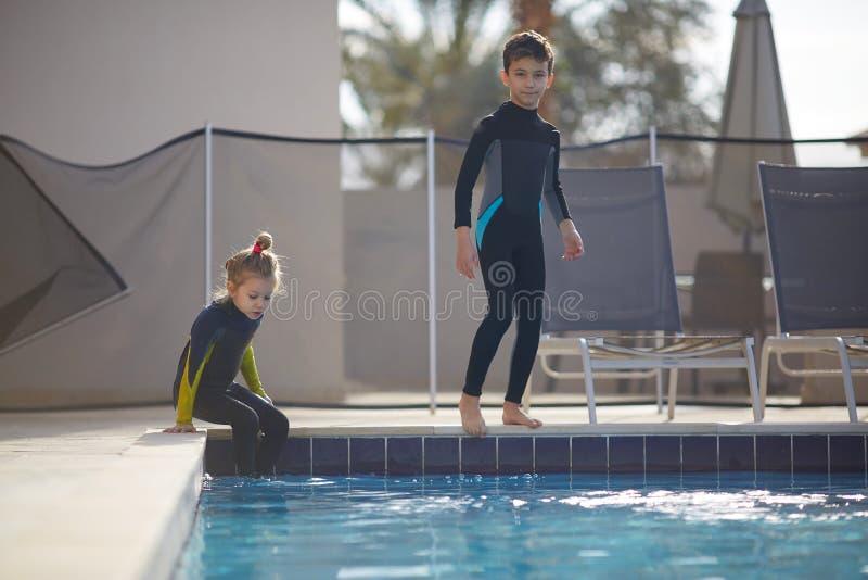Flickan och pojken förbereder sig att hoppa in i pölen royaltyfria foton