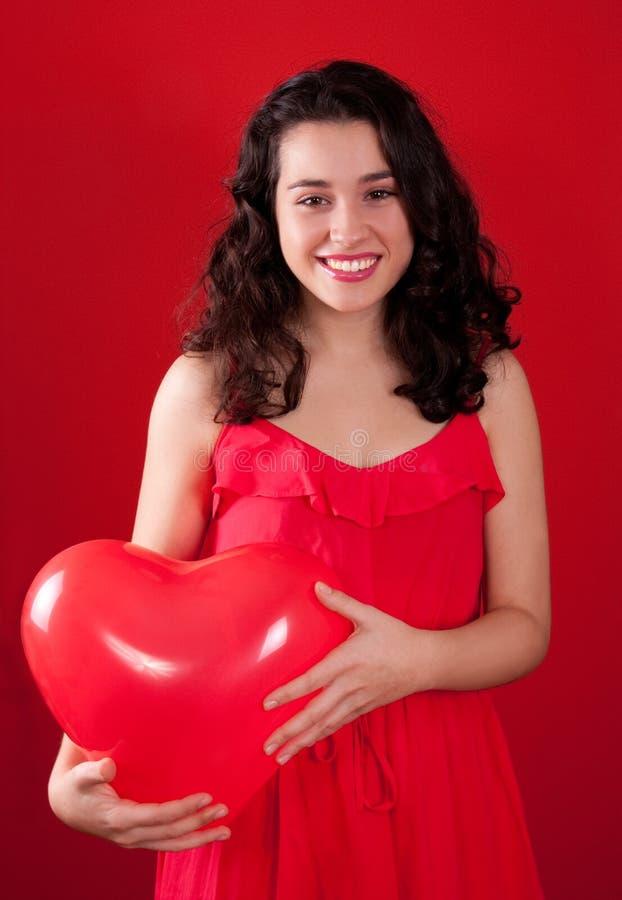 Flickan och röd hjärta formade ballongen royaltyfri foto