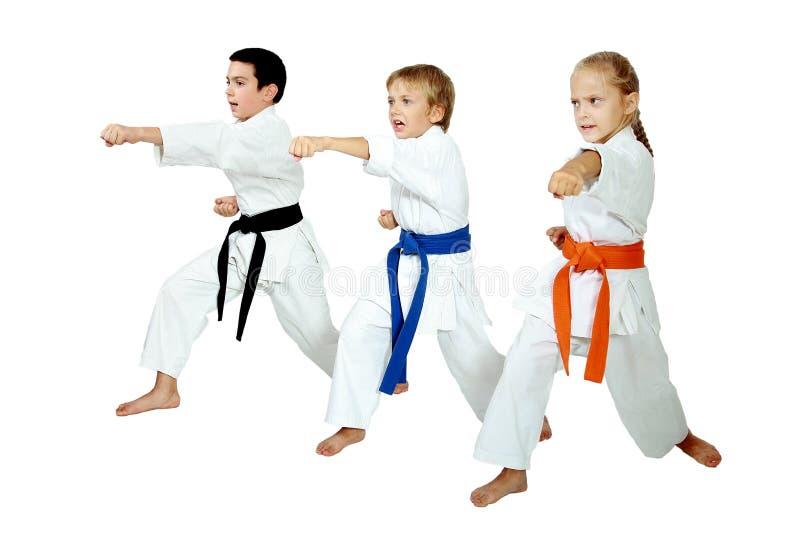 Flickan och två pojkar på en vit arm för bakgrundstaktstansmaskin arkivbilder