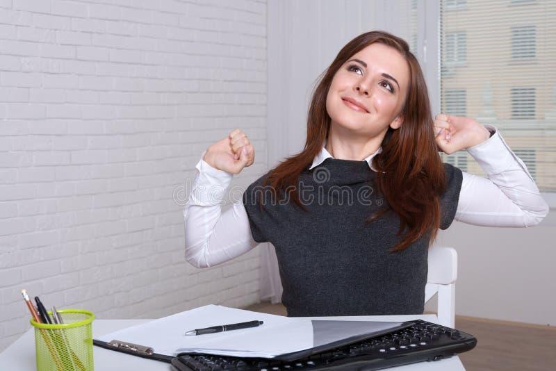 Flickan på arbetsplatsen som tröttas av arbete, sträcker royaltyfri bild