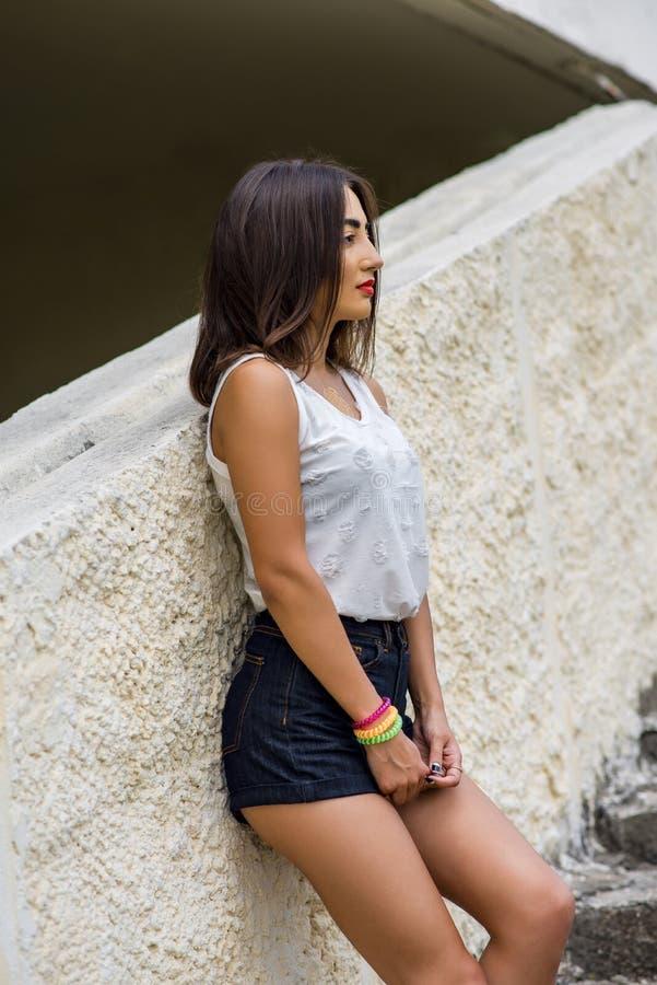 Flickan på byggnaden i en vit blus och kortslutningar, sommar i staden, livsstil, feriebegrepp fotografering för bildbyråer