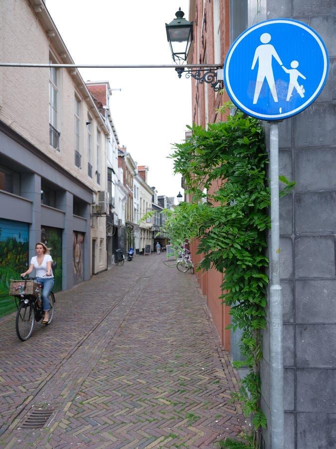 Flickan på cykeln rider till och med den gamla smala gränden i mitten av arkivfoto