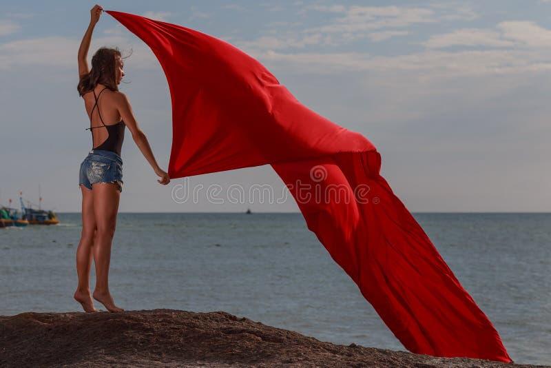 Flickan på den röda torkduken för strandwhith arkivfoton