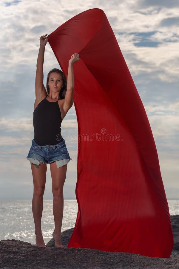 Flickan på den röda torkduken för strandwhith arkivfoto