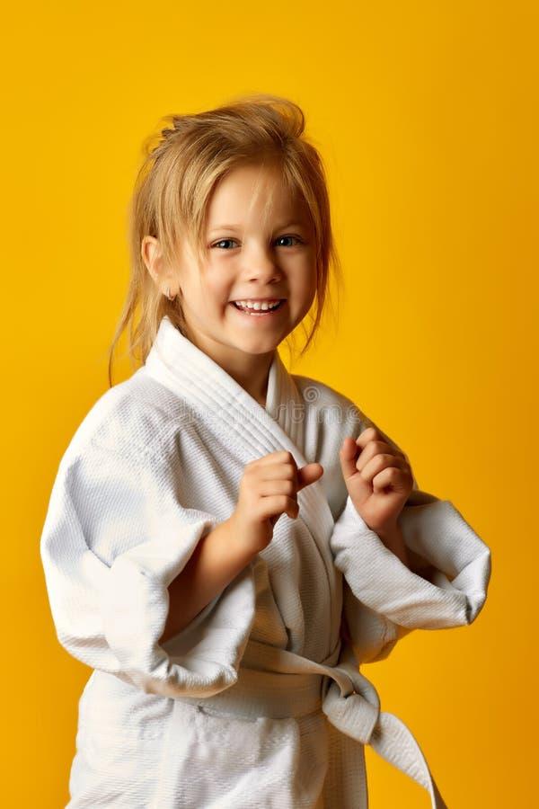 Flickan på en gul bakgrund med det vita bältet slår assistenten arkivfoto