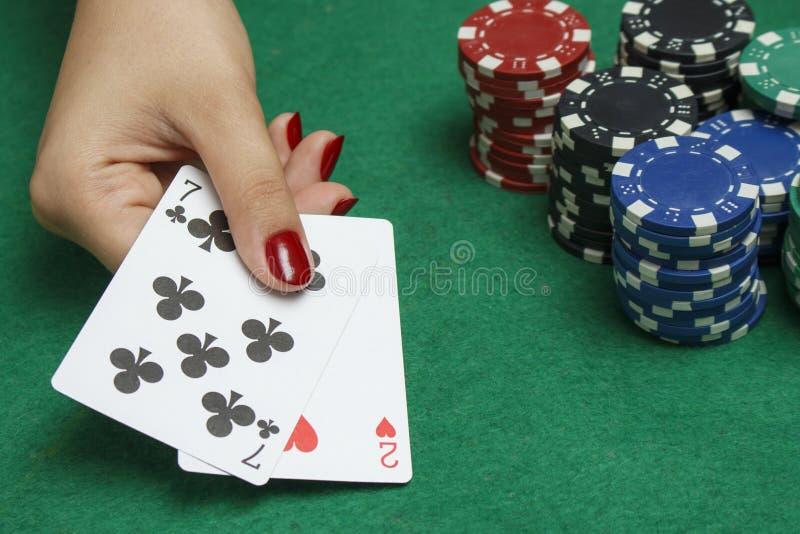 Flickan på pokertabellen rymmer kort royaltyfria foton