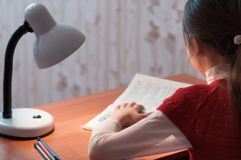 Flicka på skrivbordläsning en boka vid ljust av lampan royaltyfri bild