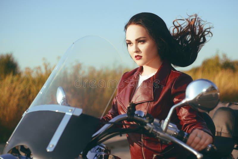 Flickan på spåret springer på en motorcykel Härlig brunett på en motorcykel Flickan med vinden i hennes hår confusedly flicka?r royaltyfria foton