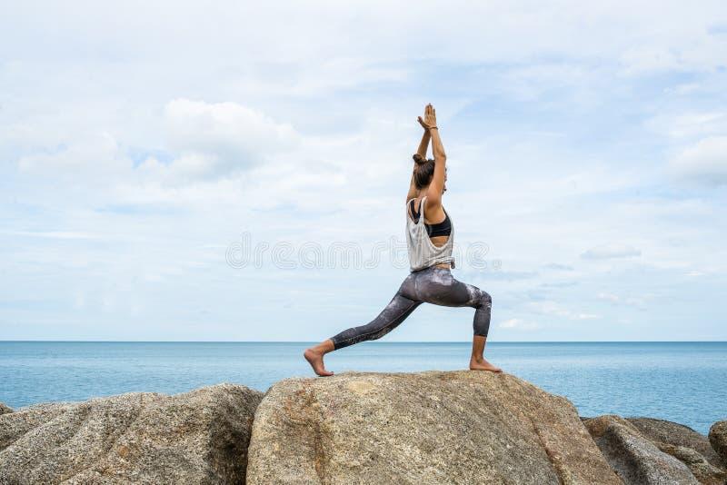 Flickan på stenar som upptar med yoga, en avrinning i Asanaen, yoga på havet, på en ponny av ett härligt landskap royaltyfria bilder