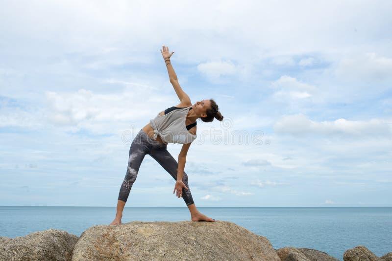 Flickan på stenar som upptar med yoga, en avrinning i Asanaen, yoga på havet, på en ponny av ett härligt landskap arkivbilder