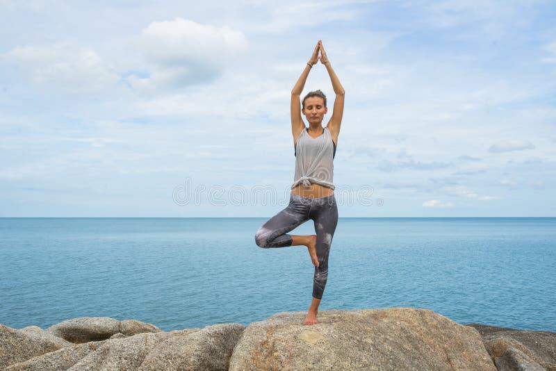 Flickan på stenar som upptar med yoga, en avrinning i Asanaen, yoga på havet, på en ponny av ett härligt landskap arkivfoto