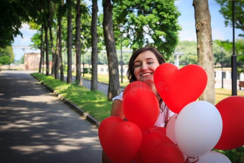Flickan parkerar in med att le för ballonger Röda och vitfärger arkivbild