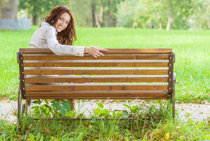 Flickan parkerar på bänken arkivfoto