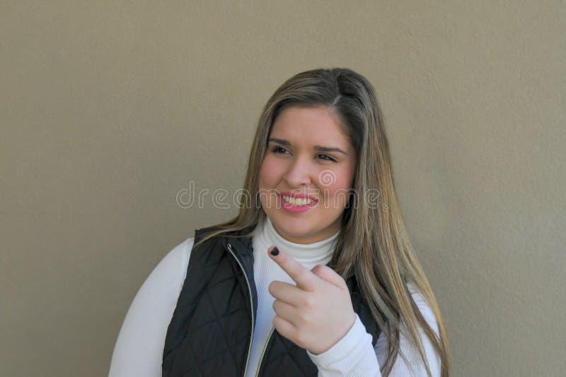 Flickan pekar hennes finger som ler på vem förbigår någonsin arkivfoton