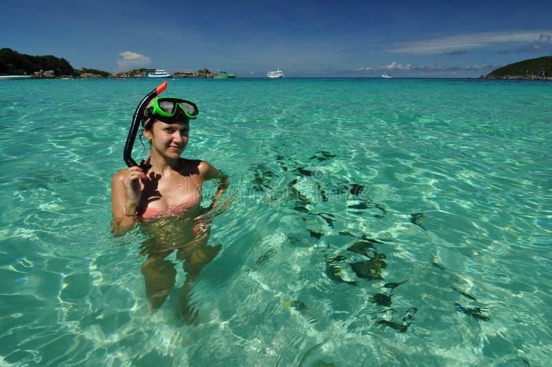 Flickan poserar i blått vatten med fiskar, når han har snorklat, Similan öar, Thailand fotografering för bildbyråer