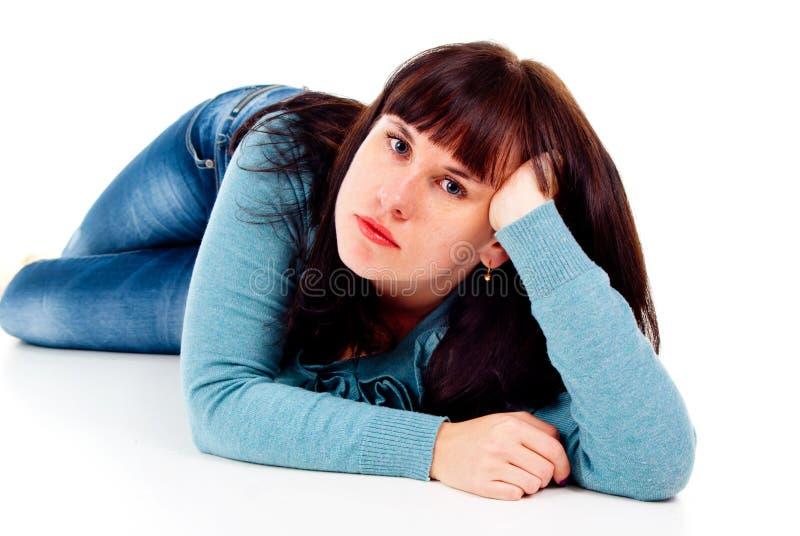 Flickan poserar, medan ligga på golvet royaltyfria foton
