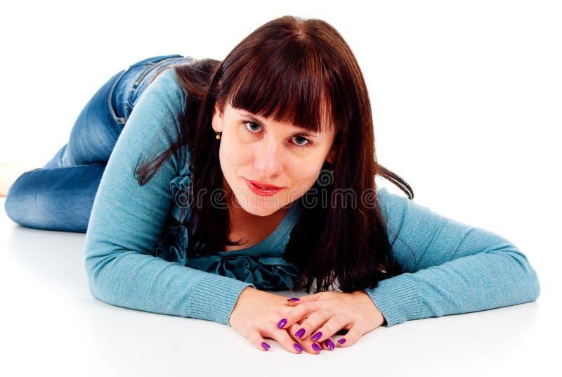 Flickan poserar, medan ligga på golvet arkivfoto