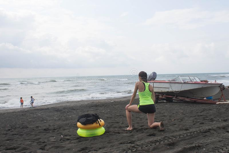 Flickan, powerboaten och guling, grön sväva cirkel på stranden som är mulen, moln, vinkar royaltyfri fotografi