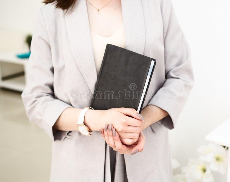 Flickan r?cker en bok i hennes h?nder, ikl?tt gr?tt omslag Hon har ett armbandsur p? hennes hand Vit bakgrund royaltyfri foto