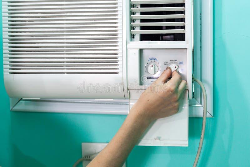 Flickan reglerar temperaturen av en liten rumluftkonditioneringsapparat royaltyfria bilder
