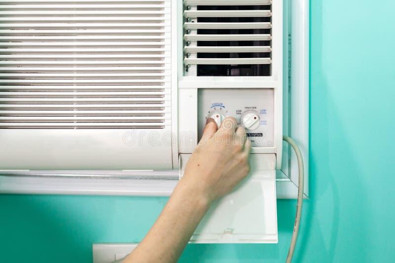 Flickan reglerar temperaturen av en liten rumluftkonditioneringsapparat fotografering för bildbyråer