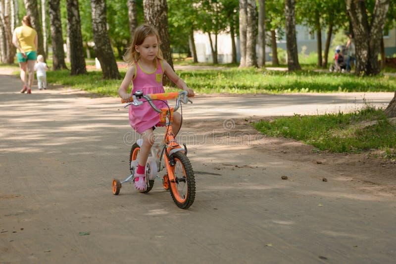 Flickan rider barns fyra-rullade cykel i parkerar arkivbild