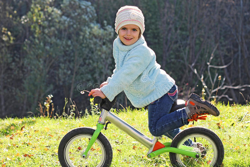 Flickan rider en cykel royaltyfri foto
